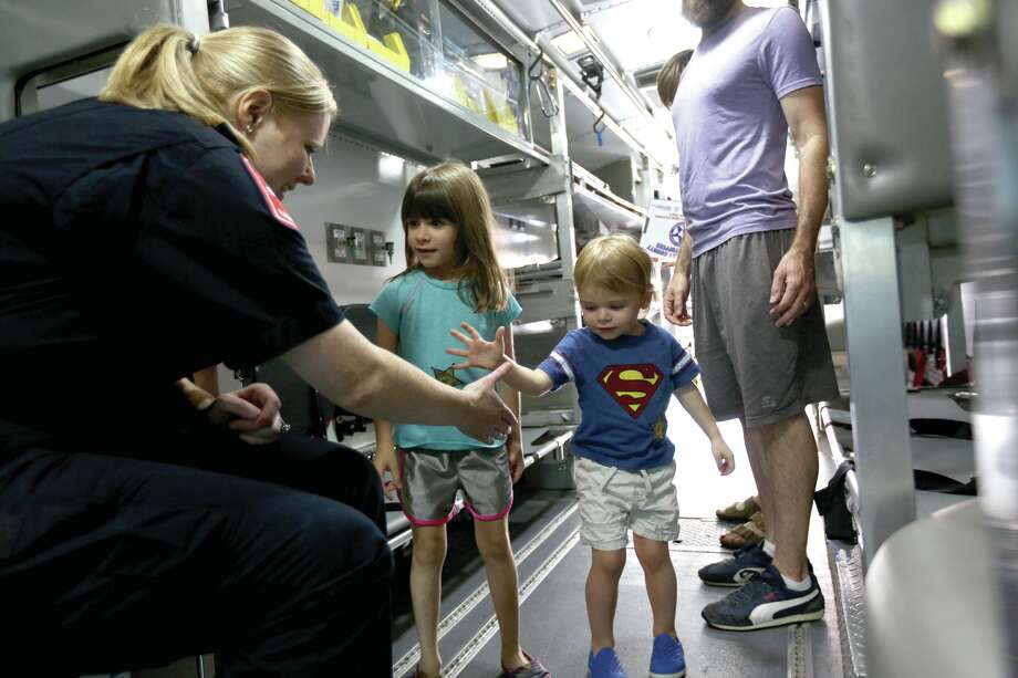 Paramedic Micah Clocksin, of the Atascocita Volunteer Fire Dept., left, chats with Parker Peschier, 5, and Mikey Peschier, 3, as they tour an AMBUS, a mass casualty unit, during a previous East 1488 Emergency Preparedness Fair at the Home Depot on FM 1488. The AMBUS can transport 14 casualties laying down, and as many as 24 while sitting. Photo: Michael Minasi, Photographer / Conroe Courier