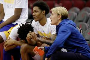 Quinn Cook, left, puts his head on Patrick McCaw as he talks wtih Chelsea Lane, head performance therapist, right, as the Golden State Warriors practiced on Sunday ahead of the Monday's Western Conference Finals game against Houston Rockets at Toyota Center in Houston, Tex., on Sunday, May 13, 2018.