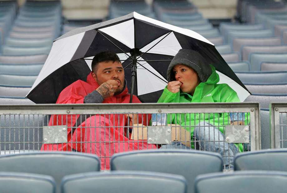 Two fans snack huddled under an umbrella during a rain-delayed baseball game between the New York Yankees and the Oakland Athletics in New York, Sunday, May 13, 2018. (AP Photo/Kathy Willens) Photo: Kathy Willens / Associated Press