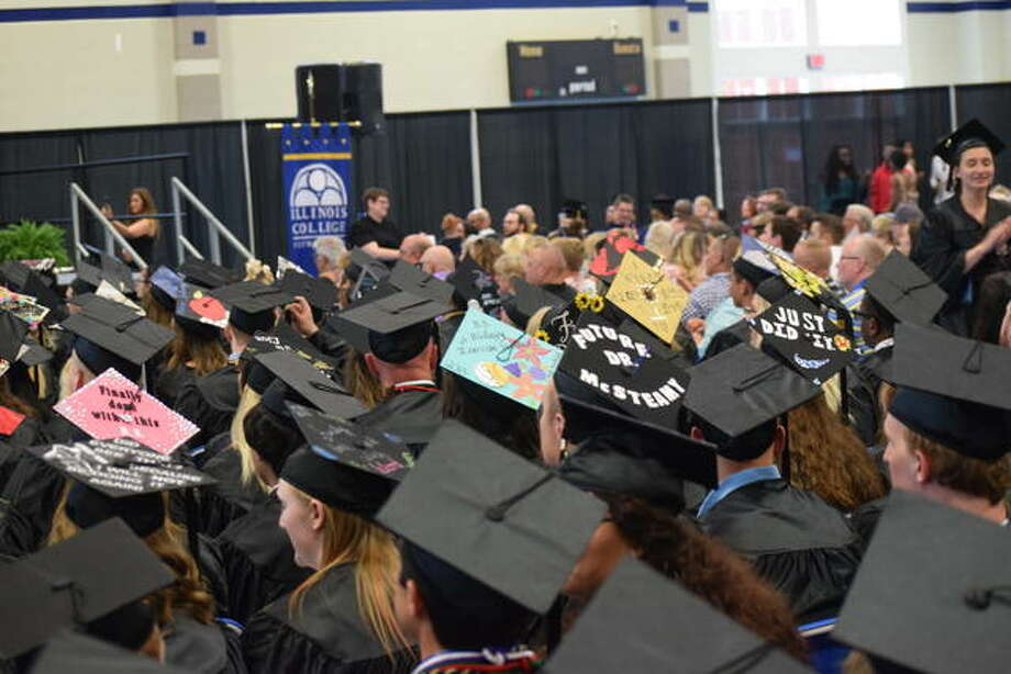 Some of the students' graduation cap decorations can be seen as students sit in the gym before the graduation ceremony Sunday. Photo:     Audrey Clayton | Journal-Courier