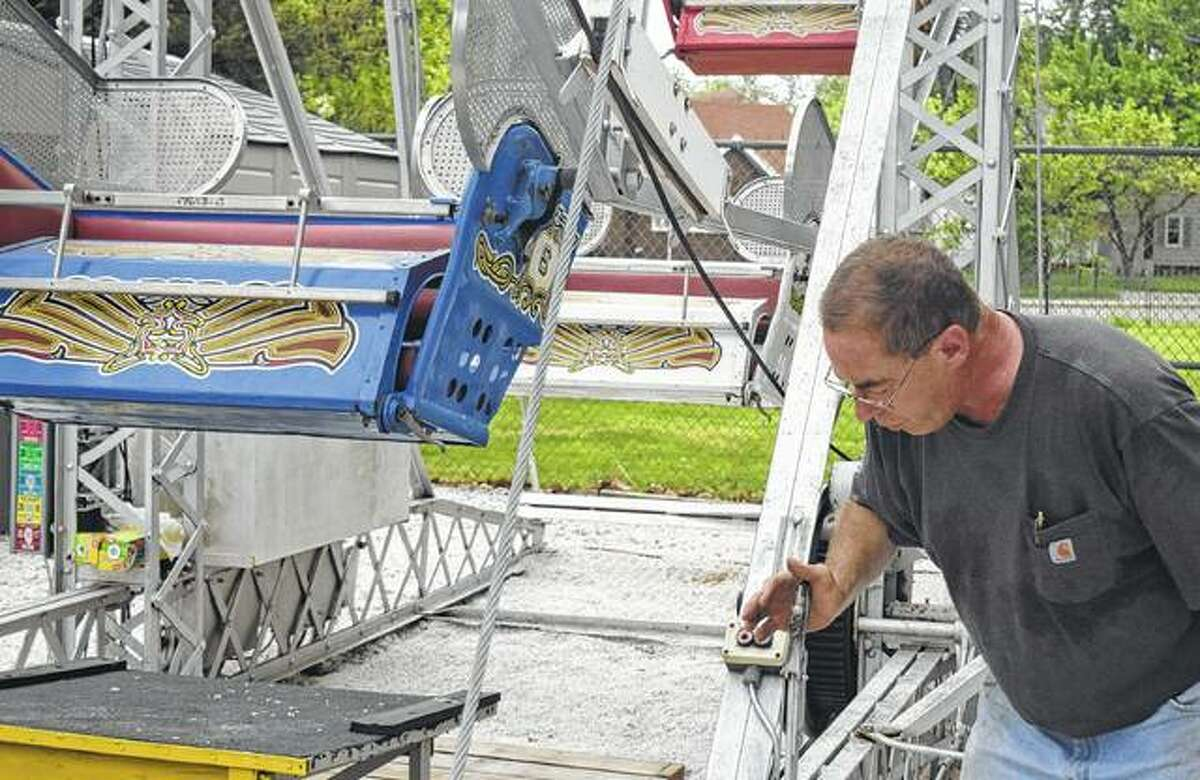 Rotarian David Fisher shows other Rotary members how to operate the Ferris wheel.