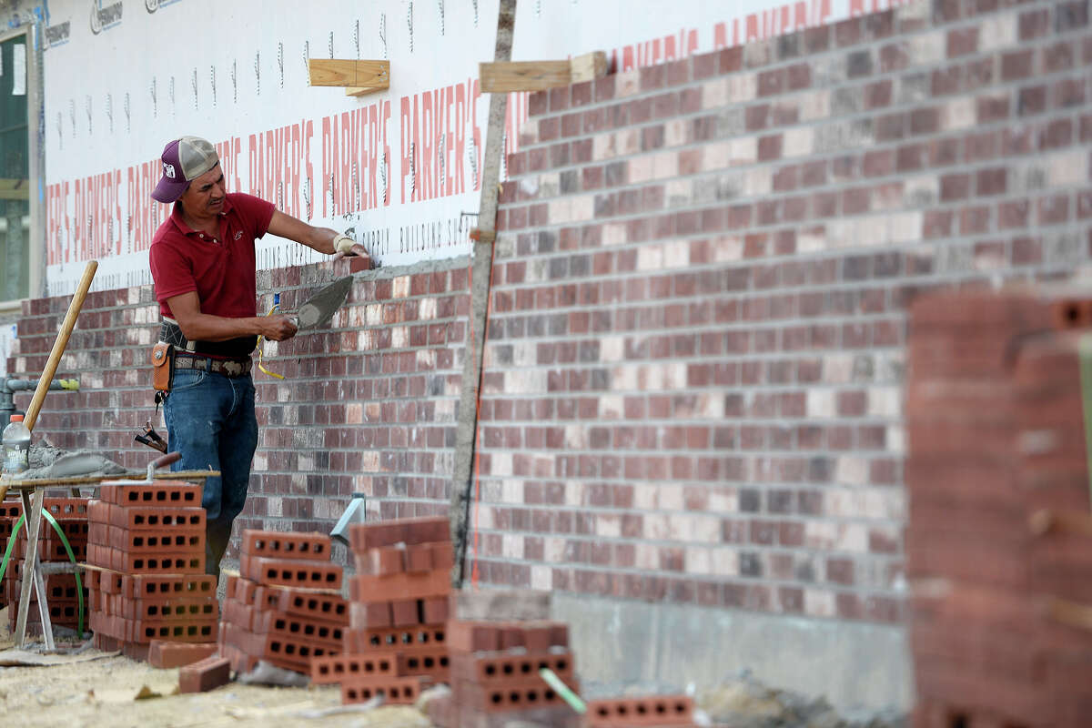 A mason works on the brick exterior wall of a house under construction in the Copper Point subdivision in Lumberton. Photo taken Friday 5/11/18 Ryan Pelham/The Enterprise