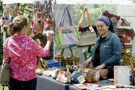 """Yvonne Zeisler, of Fairfield, left, checks out handmade purses from Our Woven Community at the annual Dogwood Festival at Greenfield Hill Congregational Church in Fairfield, Conn., on Friday May 11, 2018. Assisting Yvonne at right is Johana Rendon from Our Woven Community, which is based in Bridgeport. The festival featured a plant and garden boutique, a children's art and games area and several tents featuring baked goods and luncheon fare. Free entertainment was provided in the church sanctuary by jazz pianist """"Dr. Joe"""" Utterback. Other attractions included Kate's Corner, handmade crafts, collectibles and tag sale items ranging from golf clubs to designer clothes. All proceeds benefit local, national and international charities."""