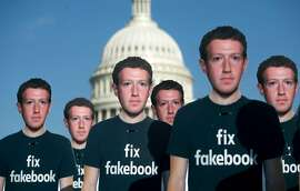 """(FILES) In this file photo taken on April 10, 2018, one hundred cardboard cutouts of Facebook founder and CEO Mark Zuckerberg stand outside the US Capitol in Washington, DC. Facebook said on may 14, 2018, it has suspended """"around 200"""" apps on its platform as part of an investigation into misuse of private user data. / AFP PHOTO / SAUL LOEBSAUL LOEB/AFP/Getty Images"""