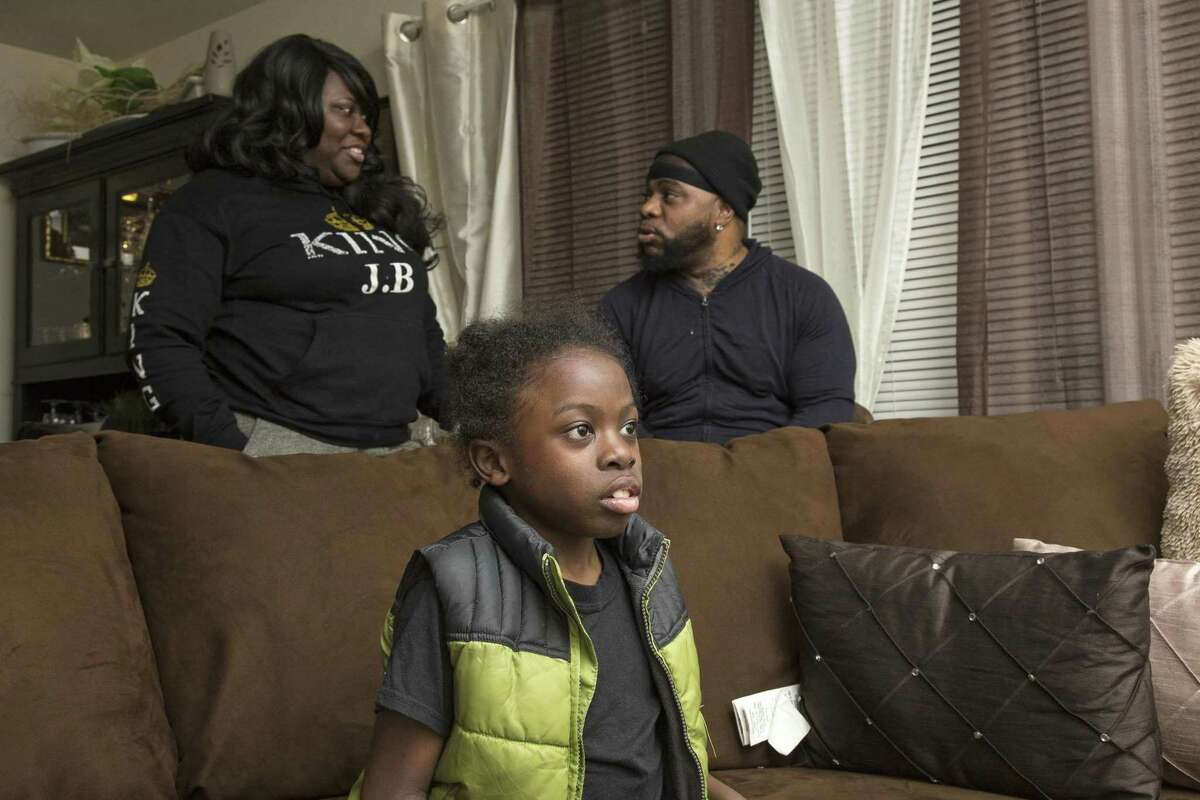 Jeremy Brown, 9, watches television with his parents, Tangi Small and Jersino Brown, in their home in Bridgeport. Jeremy has sickle cell disease, a genetic blood disorder that causes excruciating pain, life-threatening complications and a shortened life expectancy.