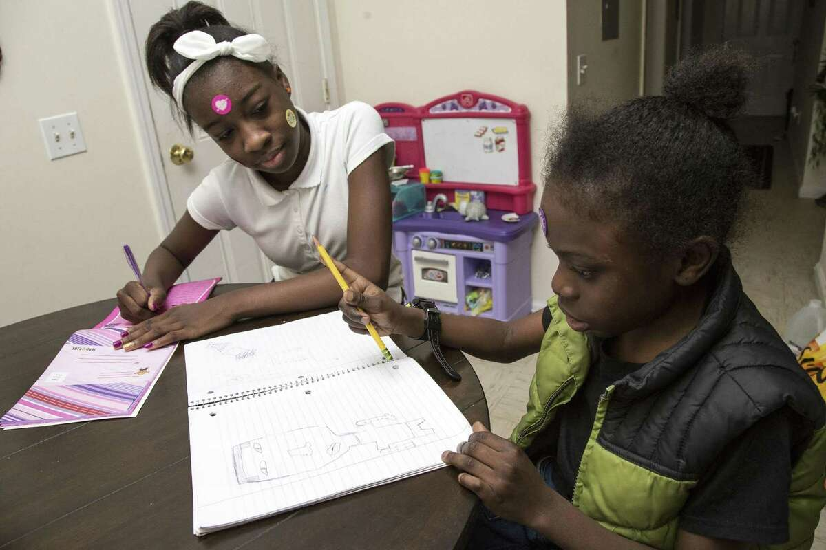 Cousins Denosh Billie, 12, and Jeremy Brown, 9, drawing and writing at their home in Bridgeport, Conn. Both have sickle-cell disease. Brown has sickle cell disease (SCD), a genetic blood disorder that causes excruciating pain, life-threatening complications and a shortened life expectancy.