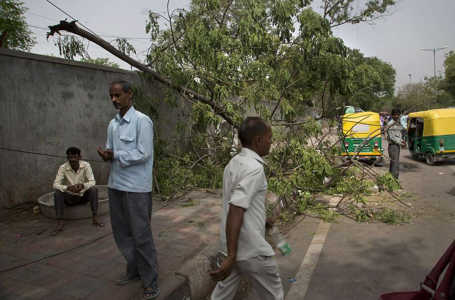 Residents examine the damage after winds uprooted a tree in New Delhi. A large swath of Uttar Pradesh state in northern India lost electricity because of so many downed power lines. Photo: Manish Swarup / Associated Press