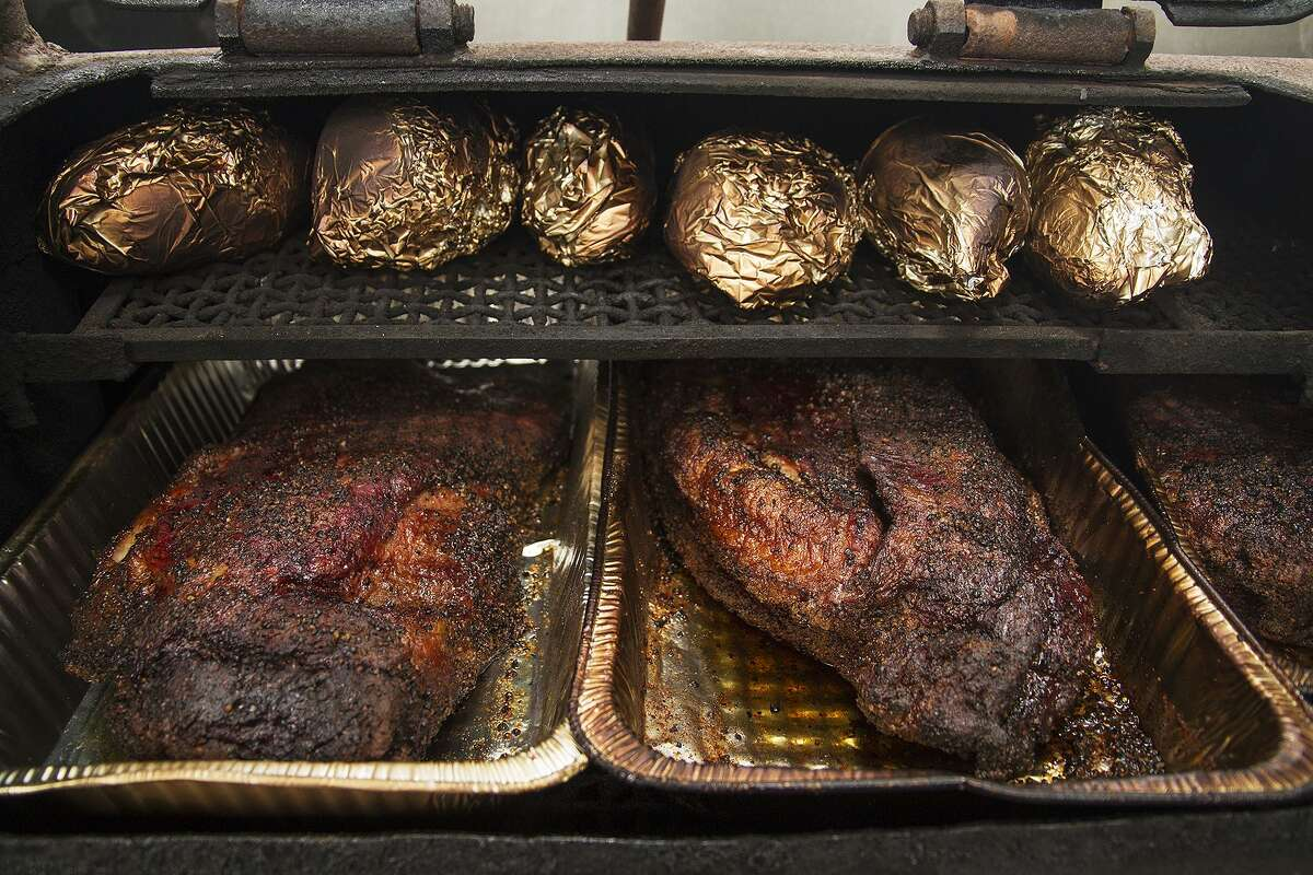 Brisket and sweet potatoes line the pit at The Dakota East Side Ice House.