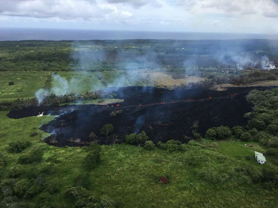 Gases rise Sunday from a fissure that opened near the town of Pahoa. Nearly 2,000 people have been told to evacuate since May 3, and lava has destroyed more than two dozen homes. Photo: U.S. Geological Survey