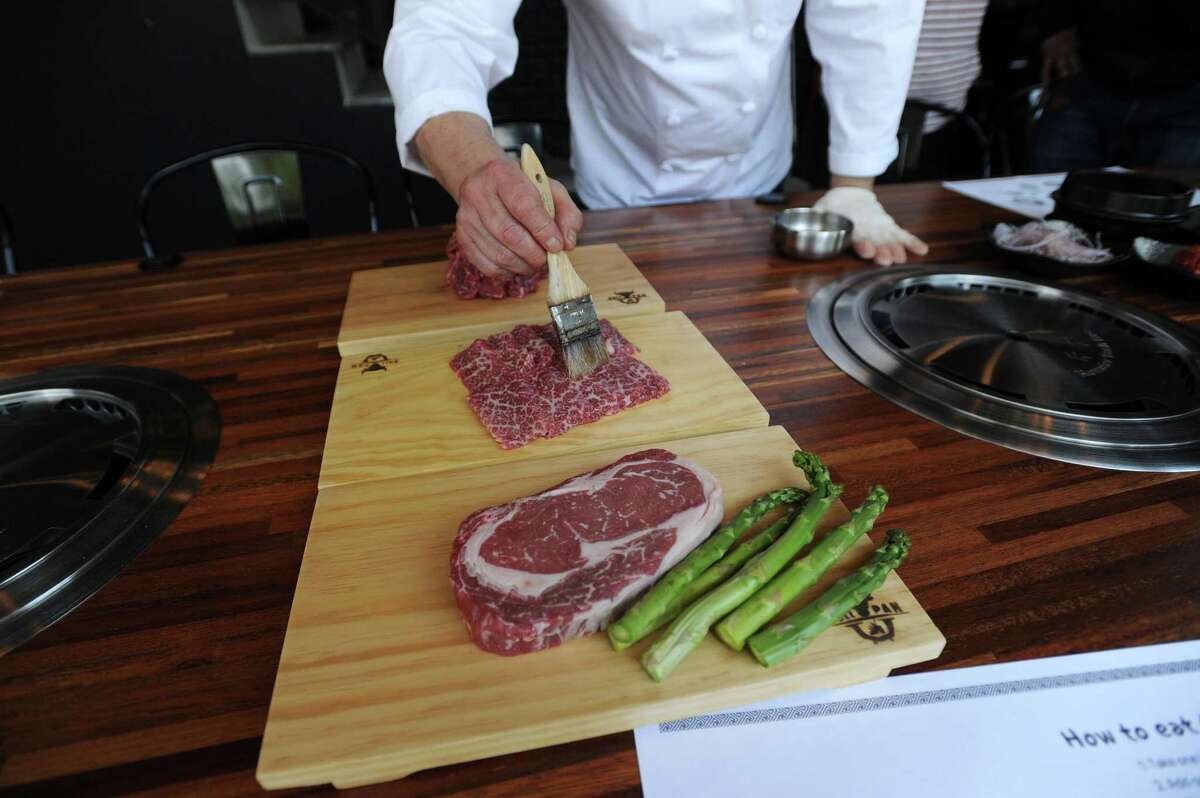 Chef Kim Yeong Gon adds flavor to a portion of meat before cooking it during a demonstration inside the the new Bull Pan Korean BBQ at 485 Summer St., in downtown Stamford, Conn., on Monday, May 7, 2018.