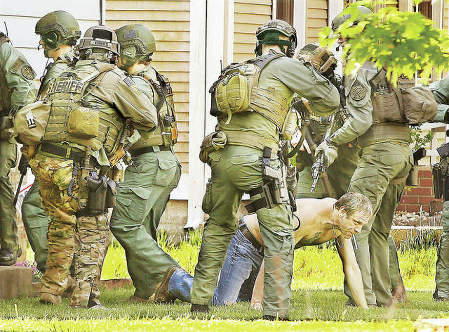 Monday morning did not start well for Thomas E. Gross as members of the ILEAS tactical team surround him after pulling him through the front door during the execution of a drug arrest warrant in the 500 block of George Street in Wood River. Gross is charged with delivery of a controlled substance within 1,000 feet of a church. Officers threw two stun grenades into the house during the raid to disorient Gross ahead of the arrest. Nobody else was in the house and Gross was taken into custody without incident. Photo:       John Badman | The Telegraph