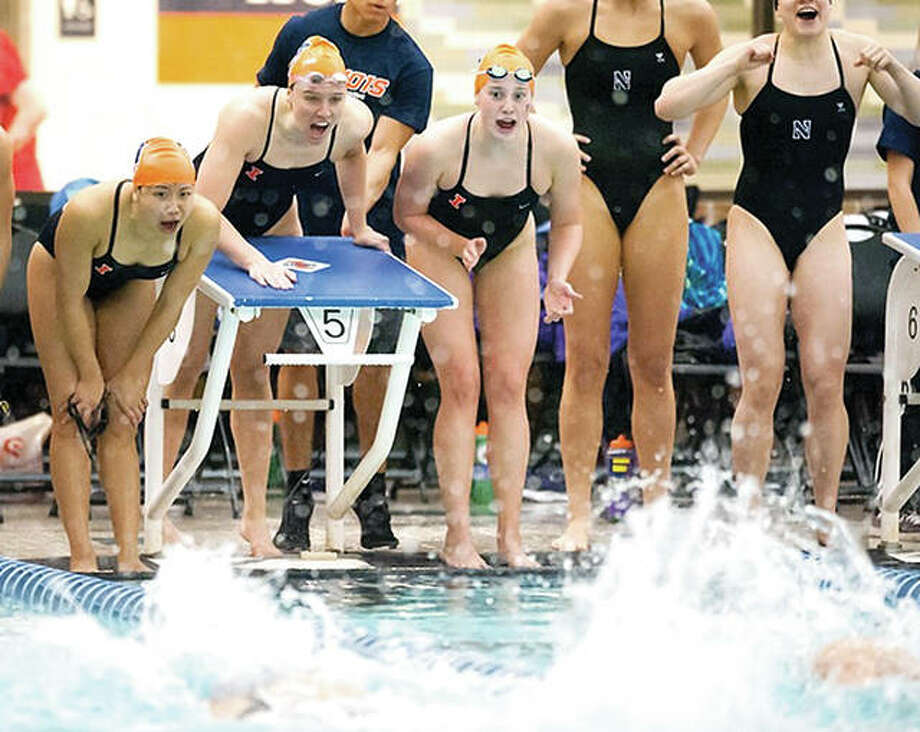 Members of the University of Illinois women's swim team cheer on a teammate during a relay this season. As part of Title IX, Illinois dropped men's swimming several years ago. Nearly 50 years ago, Title IX was enacted, in part stating that benefits for athletes must be distributed equally between what is now described as sports that earn money, such as football and basketball, vs. non-earners, which include most other sports. Photo:       Brad Leb, Illini Athletics