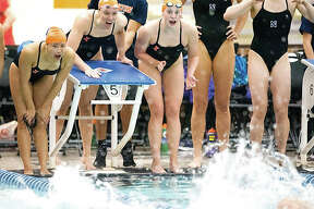 Members of the University of Illinois women's swim team cheer on a teammate during a relay this season. As part of Title IX, Illinois dropped men's swimming several years ago. Nearly 50 years ago, Title IX was enacted, in part stating that benefits for athletes must be distributed equally between what is now described as sports that earn money, such as football and basketball, vs. non-earners, which include most other sports.