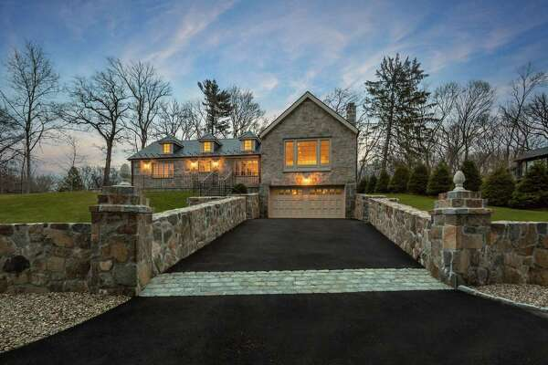 The stone cottage with beige trim and a slate roof at 235 Tokeneke Road (Route 136) has eight rooms and 2,000 square feet of living space.
