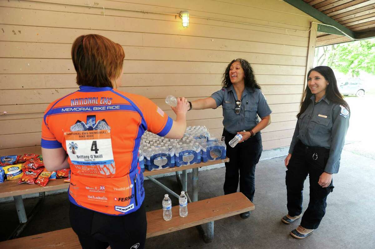 Stamford EMR Yesenia Rivera, center, and EMT Francine Mandfredi, hand out bottles of water to bicyclists during a planned stop on their National EMS Memorial Bike Ride at Cove Island Park in Stamford, Conn. on Monday, May 14, 2018.
