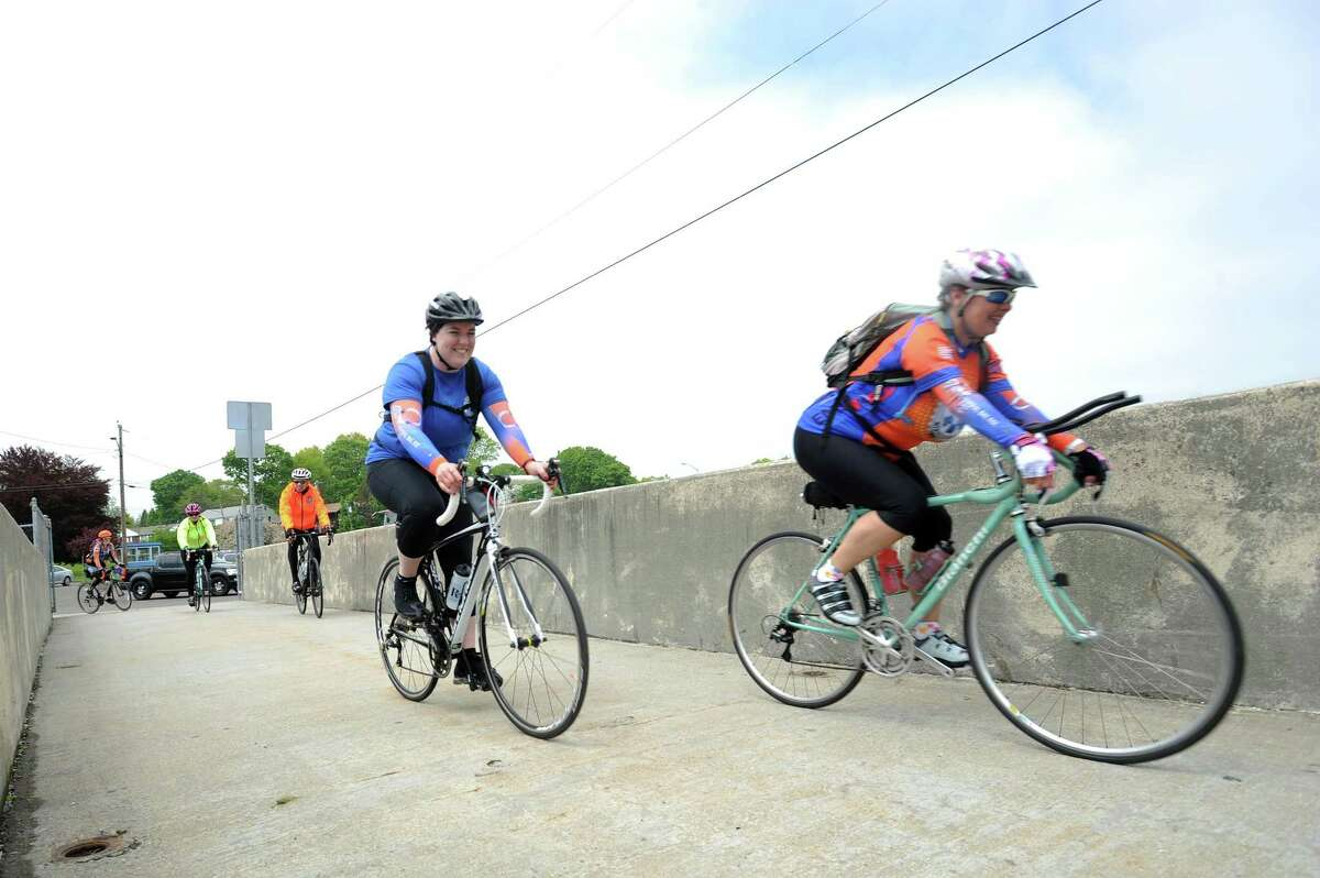 EMTs Kathleen Howard of Yonkers, N.Y. (center) and Nikki Deshensky of Harrison, N.Y. (right) enter Cove Island Park during a planned stop on the National EMS Memorial Bike Ride, which honors Emergency Medical Services personnel that died in the past year, in Stamford, Conn. on Monday, May 14, 2018. Howard and Deshensky were two of more than one hundred bicyclists that will make the approximately 500 mile journey from Boston, Mass. to National Harbord, Md.