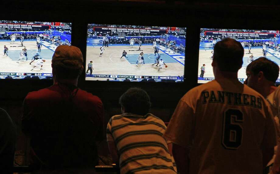 Gamblers at the Mirage Sports Book in Las Vegas, Nevada, keep a close watch on the Michigan State vs.Temple, a first round game, as the 2008 NCAA basketball tournament tips off. The Supreme Court has struck down a federal law that bars gambling on football, basketball, baseball and other sports in most states, giving states the go-ahead to legalize betting on sports. Photo: Michael Macor / San Francisco Chronicle / San Francisco Chronicle