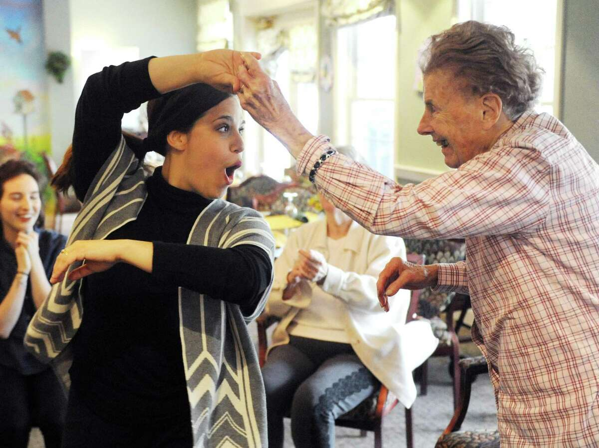 Program Director Beth Liebowitz, left, dances with resident Sonya Meurer during the creative arts therapy program at The Greens at Greenwich in Greenwich, Conn. Monday, May 14, 2018. More than 30 residents are enrolled in the program, which aims to circumvent the effects of dementia and stroke by opening up a new form of communication through music and art.