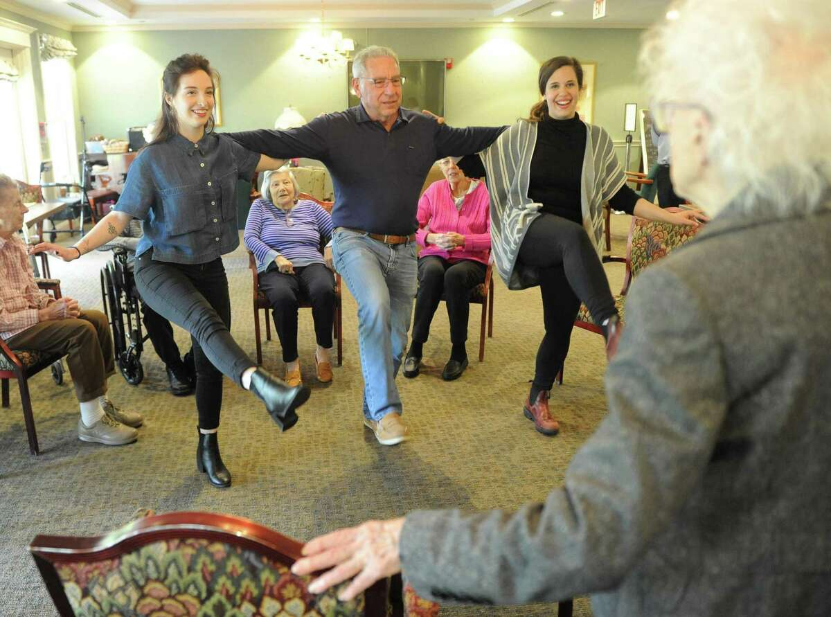 Intern Grace Rezendes, left, resident Peter Schwartz, and Program Director Beth Liebowitz get dance lessons from former Rockettes dancer, Virginia Barrett, during the creative arts therapy program at The Greens at Greenwich in Greenwich, Conn. Monday, May 14, 2018. More than 30 residents are enrolled in the program, which aims to circumvent the effects of dementia and stroke by opening up a new form of communication through music and art.