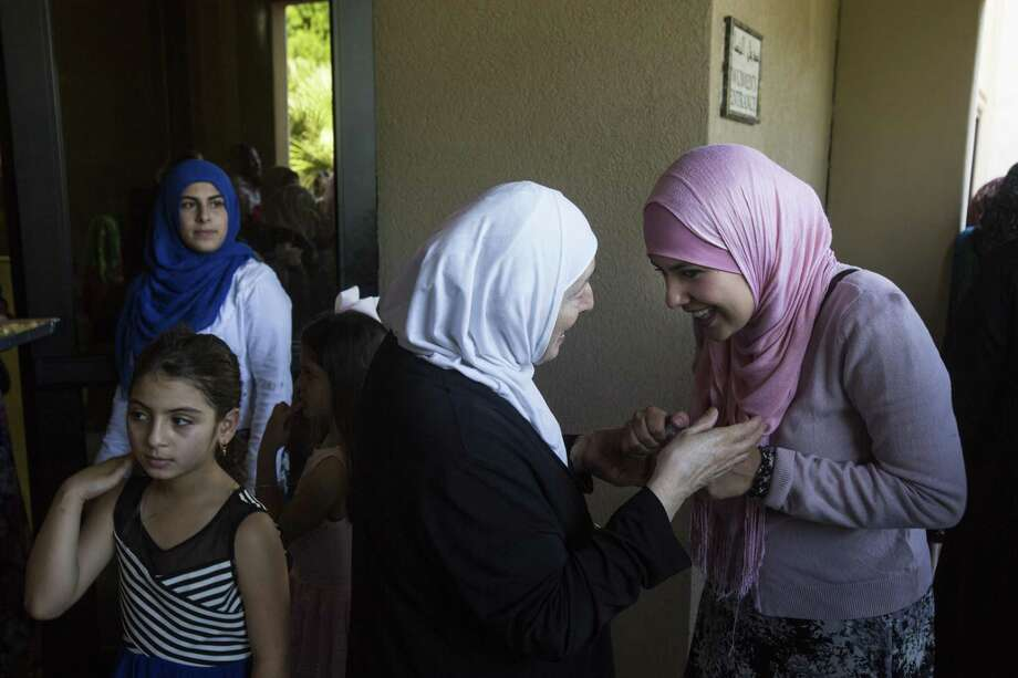 Women greet each other as members of the congregation gather outside the mosque following a communal morning prayer for the conclusion of Ramadan at the Islamic Center of San Antonio on Wednesday, July 6, 2016. Photo: BRITTANY GREESON, Staff / San Antonio Express-News / © 2016 San Antonio Express-News