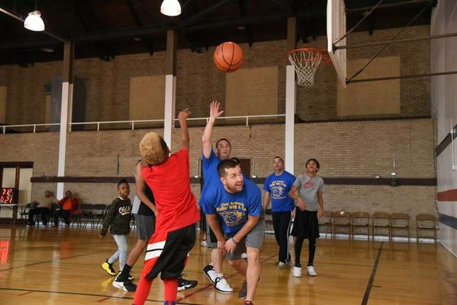 "Riley Smith, left, takes a shot as members of the Alton Police Department team try in vain to defend him during a ""Ballin' with a Cop"" event in November 2016. The next event will be May 26 at the Alton YWCA. Photo:       Kevin Korinek 