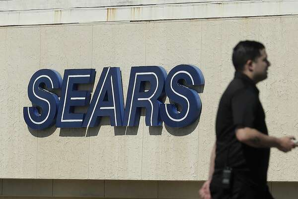 FILE- In this March 28, 2018, file photo, a man walks in front of a Sears sign in San Bruno, Calif. In a move announced Monday, May 14, Sears Holdings Corp. says a special committee of its board is starting a formal process to explore the sale of its Kenmore brand and related assets. (AP Photo/Jeff Chiu, File)