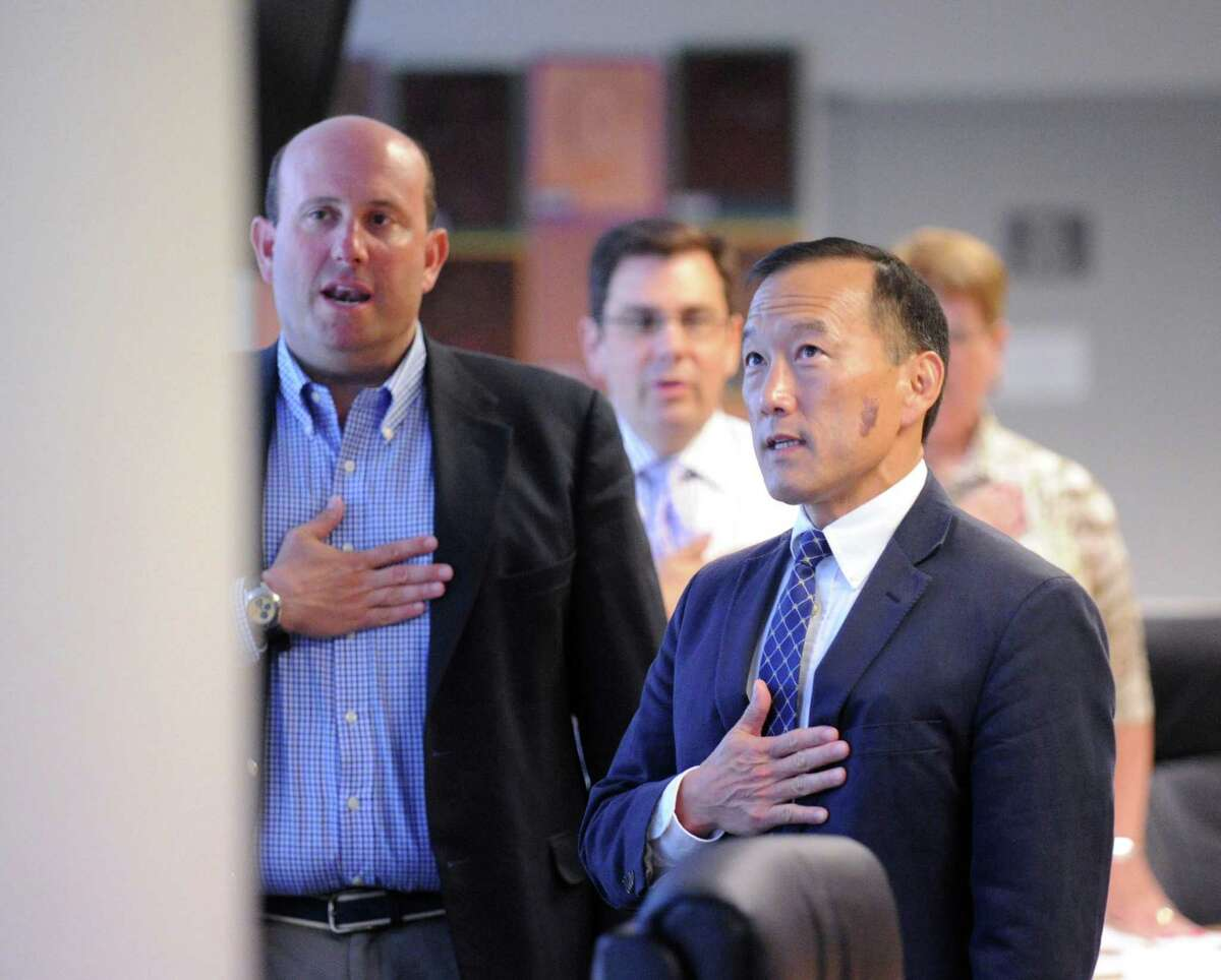 FILE - This file photo shows Stamford schools superintendent Earl Kim, right, reciting the Pledge of Allegiance during the start of his first board of education meeting at the government center. At left is Geoff Alswanger, the former board of education president.