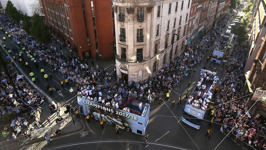 Manchester City players wave to fans from open-top buses during the the British Premier League champions trophy parade through Manchester, England. Photo: Danny Lawson / Associated Press