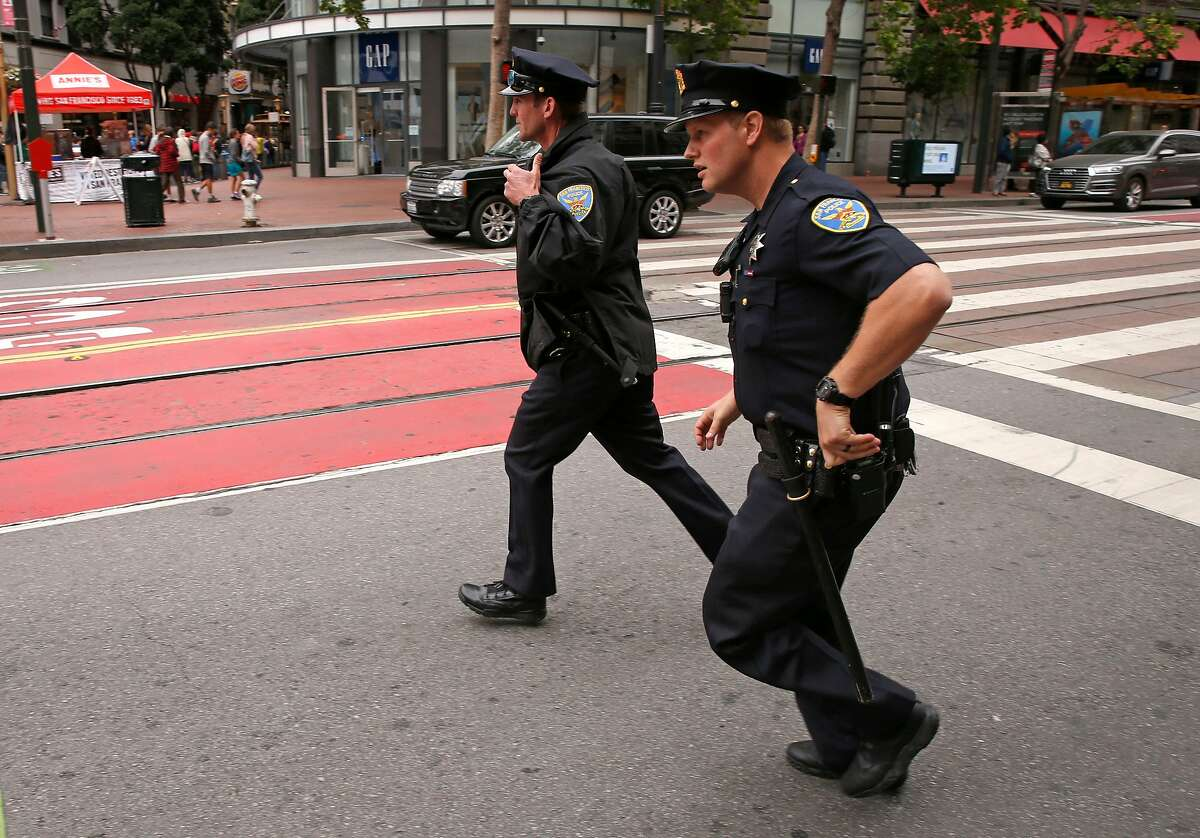 San Francisco police officers Roan, (left) and Doiron respond to a call along Market St. in San Francisco, Ca. on Mon. May 14, 2018.