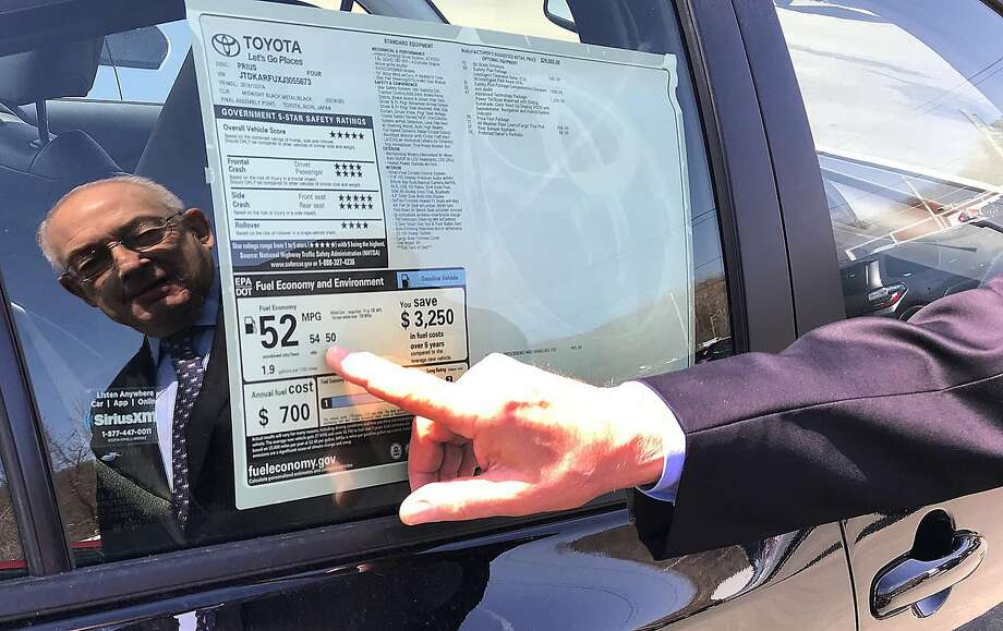Harold Tananbaum, owner of Greentree Toyota in Danbury, Conn., points to the fuel efficiency of a Prius on his lot on Wednesday, April 11, 2018. Photo: Chris Bosak, Hearst Connecticut Media