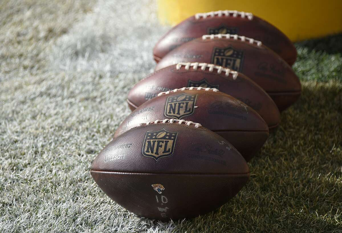 FILE - In this Jan. 14, 2018 file photo, NFL footballs sit on the field during warm ups before an NFL divisional football AFC playoff game between the Pittsburgh Steelers and the Jacksonville Jaguars in Pittsburgh. The NFL wants Congress to enact a framework for legalized sports betting in the wake of a Supreme Court ruling that clears the way for more states to allow gambling. All the major leagues responded to a ruling that figures to have far-reaching implications throughout the sports world. (AP Photo/Don Wright, File)
