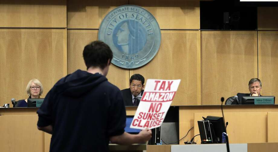 """City council members Sally Bashaw, left, President Bruce Harrell and Mike O'Brien look on as a man testifies at a Seattle City Council meeting where the council was expected to vote on a """"head tax"""" Monday, May 14, 2018, in Seattle. (AP Photo/Elaine Thompson) Photo: Elaine Thompson/AP"""