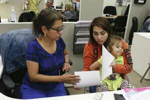 Twenty-two-year-old Sky Gomez holds her daughter, Gisselle Metoyer, 3, as she gets help renewing her Supplemental Nutrition Assistance Program benefits from Annie Gonzales, Client Service Representative at the San Antonio Food Bank, Monday, May 14, 2018. Texas administers over $410 million in SNAP benefits each month, mostly to low-income children and families. The program, formerly known as food stamps, is funded entirely by federal dollars.