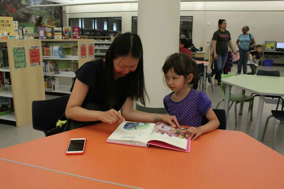 Janice Chuang, left, sits at a table to read a book about Disney princesses to her daughter, Izzy Jones, in the children's section of the Barbara Bush Branch Library. The library opened on Monday after sustaining major flood damage from Hurricane Harvey. Photo: Mayra Cruz