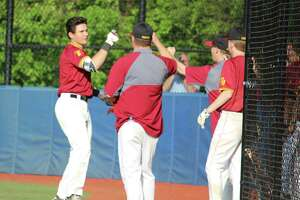St. Joseph third baseman Charlie Pagliarini (left) celebrates with coaches after hitting a two-run in the sixth inning during an FCIAC baseball game between Darien and St. Joseph on May 14, 2018 at Darien High School in Darien, Conn. St. Joseph defeated Darien 8-4.