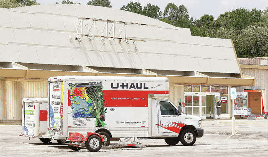 A worker cleans near the front door of the old Kmart store, which opened in Alton Friday as a U-Haul facility. Renovations are planned once U-Haul buys Seminary Plaza, where the building is located. Photo:       John Badman | The Telegraph