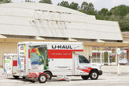 A worker cleans near the front door of the old Kmart store, which opened in Alton Friday as a U-Haul facility. Renovations are planned once U-Haul buys Seminary Plaza, where the building is located.