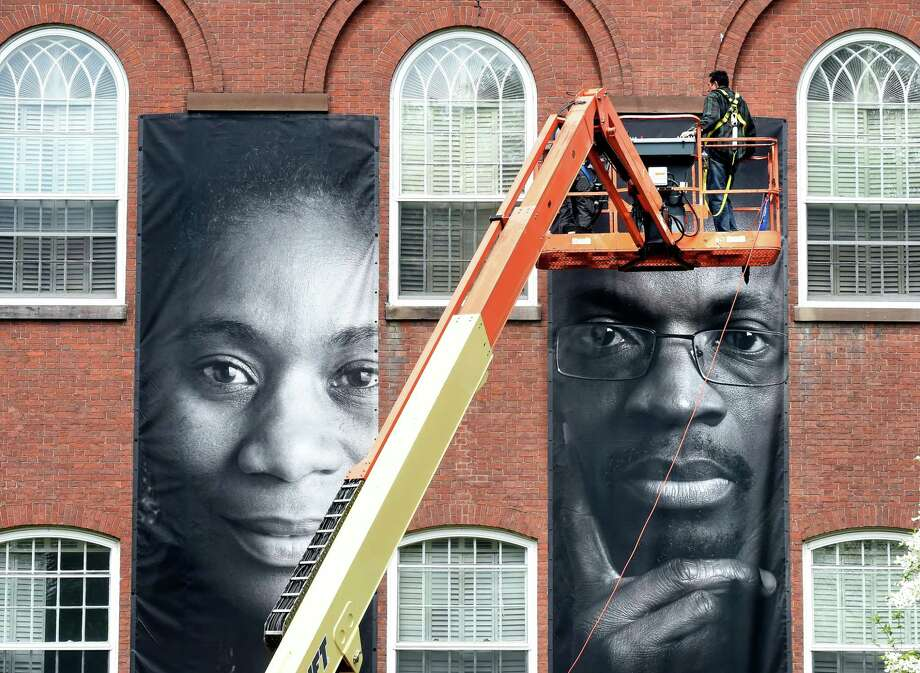 Workers install portraits of immigrants on United Church on the Green in New Haven Monday. Photo: Arnold Gold / Connecticut Hearst Media / New Haven Register
