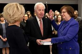 In this photo provided by the New York Attorney General's Office, Solicitor General Barbara Underwood, right, takes the oath of office at the State Capitol in Albany, N.Y., Tuesday, May 7, 2018. Underwood became the state's acting Attorney General after Eric Schneiderman resigned amid accusations of abusing four women during intimate encounters. From left is New York Chief Judge Janet DiFiore, Underwood's husband Martin Halpern and Barbara Underwood. (New York Attorney General's Office via AP)