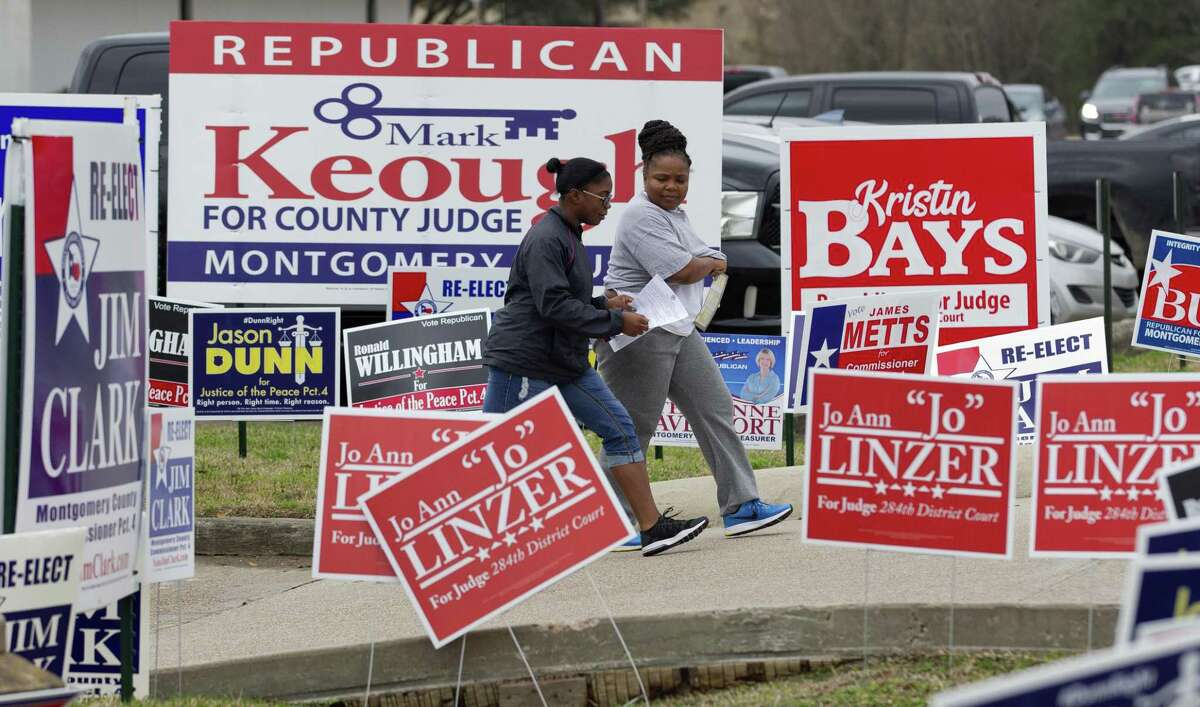 Voters walk by political signs that line the street to the East Montgomery County Courthouse on the first day of Early Voting, Tuesday, Feb. 20, 2018, in New Caney.