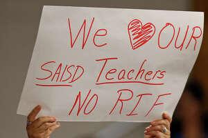 People hold signs during the SAISD board meeting held Monday May 14, 2018 at  at the David G. Burnet Center.