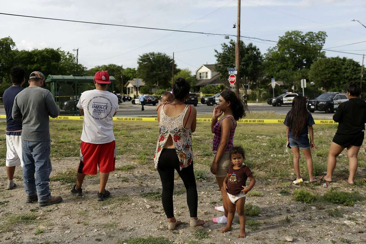 Area residents watch as officers investigate the scene of an officer involved shooting off Iowa Street on the East Side of San Antonio on Monday, May 14, 2018.