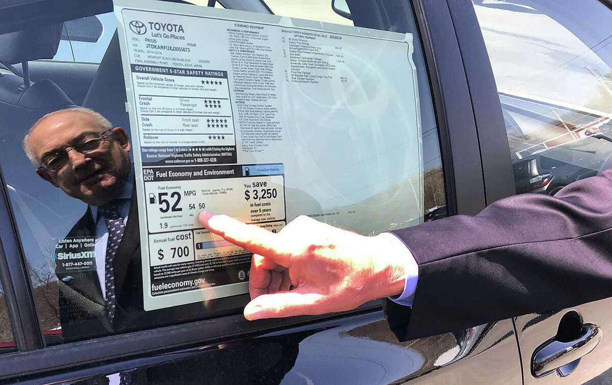 Harold Tananbaum, owner of Greentree Toyota in Danbury, Conn., points to the fuel efficiency of a Prius on his lot on Wednesday, April 11, 2018.