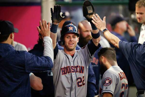 Houston Astros' Josh Reddick, center, is greeted by teammates after he scored on a single by Max Stassi during the third inning of a baseball game against the Los Angeles Angels, Monday, May 14, 2018, in Anaheim, Calif. (AP Photo/Jae C. Hong)