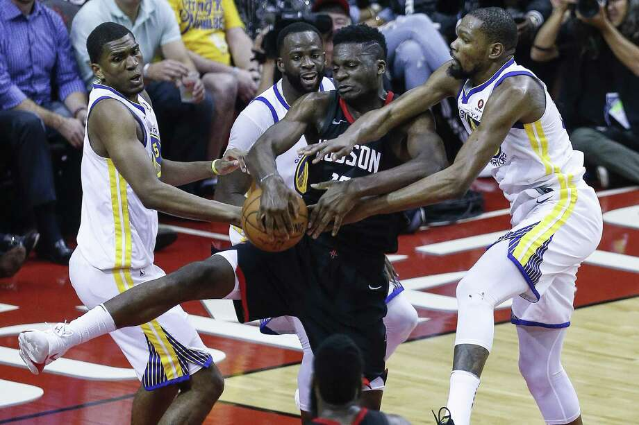 Rockets center Clint Capela gets entangles with, from left, the Warriors' Kevon Looney, Draymond Green and Kevin Durant in the battle for a second-half rebound. Photo: Michael Ciaglo, Houston Chronicle / Houston Chronicle / Michael Ciaglo