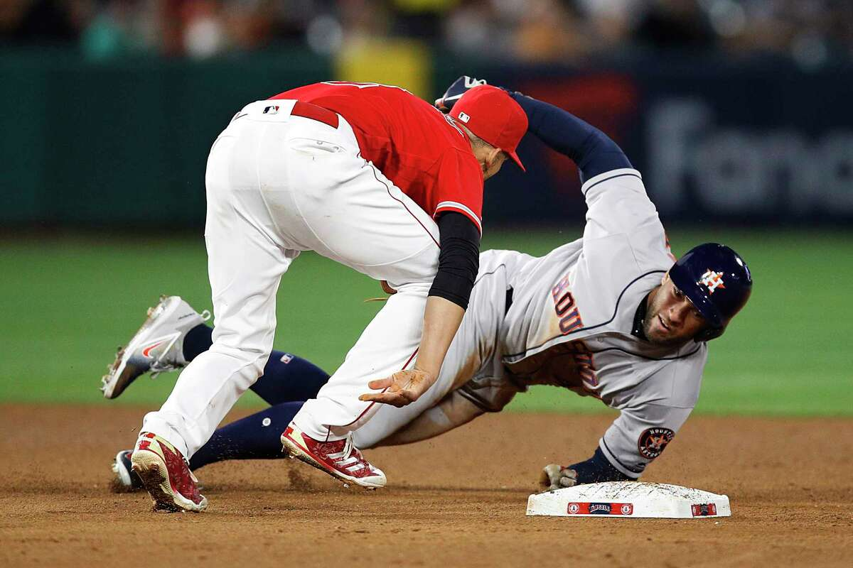 Houston Astros' George Springer, right, is tagged out by Los Angeles Angels' Andrelton Simmons during the ninth inning of a baseball game, Monday, May 14, 2018, in Anaheim, Calif. The Angels won 2-1. (AP Photo/Jae C. Hong)