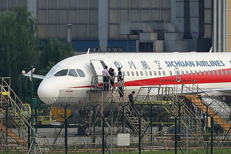 "This photo taken on May 14, 2018 shows employees checking a Sichuan Airlines Airbus A319 after an emergency landing, as a broken cockpit window (L) is covered, in Chengdu in China's northwestern Sichuan province.  The pilot who made an emergency landing in southwest China after a broken cockpit window sucked his co-pilot halfway out of the aircraft was hailed as a ""hero"" on May 15 by astonished citizens. All 128 people aboard the Airbus A319 of Sichuan Airlines survived the ordeal. / AFP PHOTO / - / China OUT-/AFP/Getty Images Photo: -, AFP/Getty Images"