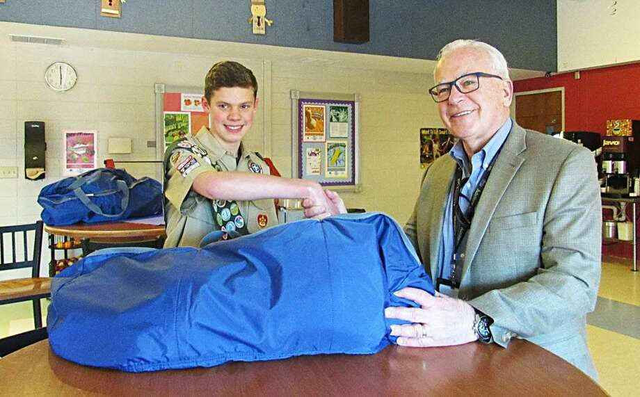 For his Eagle Scout project, Evan Coppa of Wethersfield, at left, put together assembled duffle bags for residents of Ädelbrook in Cromwell. At right is Garry Mullaney, president and CEO. Photo: Contributed Photo