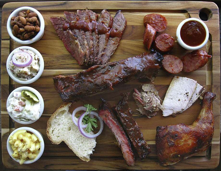 Barbecue and sides from the County Line. Clockwise from top left: beans, brisket sausage, barbecue sauce, turkey, chicken, pork spare ribs, homemade bread, mac and cheese, cole slaw and garlic mashed potatoes Photo: Mike Sutter /San Antonio Express-News