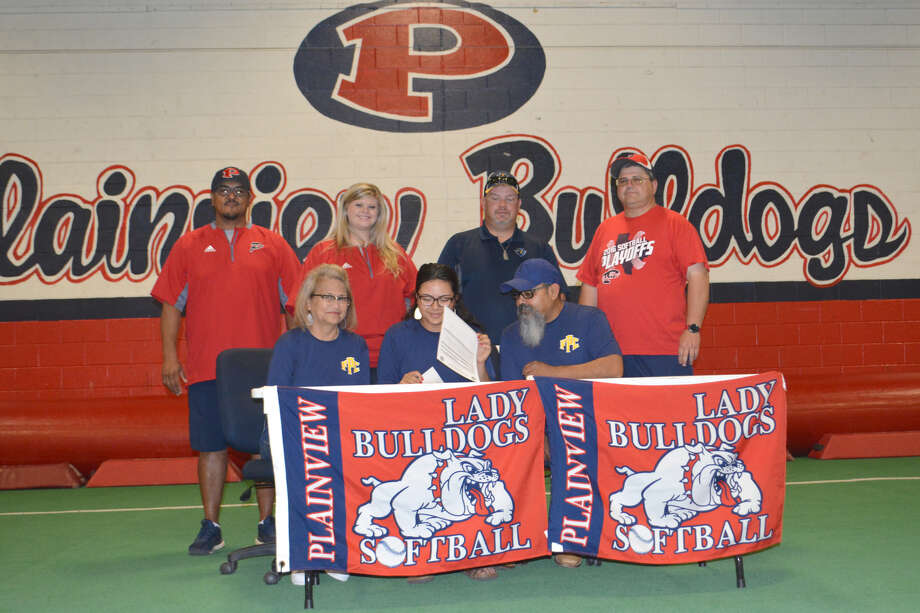 With her parents Carmen and Johnny Perez at her side, Plainview High School Lady Bulldog softball player Trini Perez looks for more places to sign a letter committing her to play next season at Frank Phillips College in Borger for the Lady Plainsmen. Looking on are Lady Dogs assistant coaches Enrique Villa (standing left) and Kami Carnell; Frank Phillips head softball coach Lucas Grider and Lady Dogs varsity coach Johnny Hill.